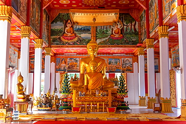 Wat Si Saket, a large golden Buddha statue and altar with offerings and wall murals, Vientiane, Laos, Laos