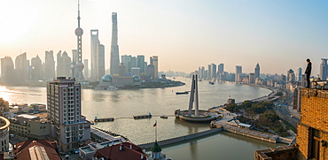 Man admiring view over Huangpu River & Shanghai skyline in early morning, Shanghai, China, China