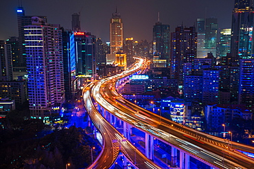 Elevated view of stacked road junction & Shanghai skyline at dusk, Shanghai, China, China