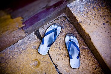 High angle close up of pair of worn down blue sandals outside on a doorstep, India, Rajasthan