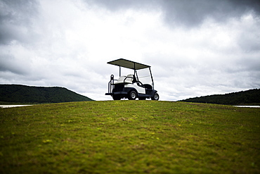 Golf cart parked on the green of a golf course under a cloudy sky, Vietnam