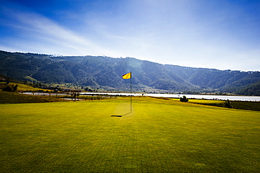 Flag on a golf course with sea and mountains in the distance, Vietnam