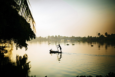 Local fisherman rowing a boat on a river in the early morning hours, Vietnam