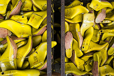 High angle close up of bins of yellow shoe molds in a factory, Vietnam