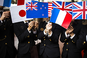 Close up of people in uniform waving small national flags, Kyushu, Japan