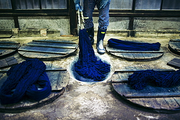 Close up of man beating indigo dye into strands of cotton, Kyushu, Japan