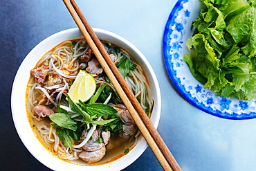 High angle close up of a bowl of bun bo hue, or beef noodle soup, Vietnam