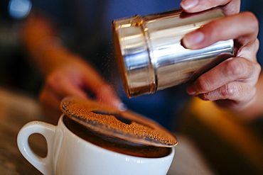 Close up of barista putting the finishing touches on a mocha, Vietnam