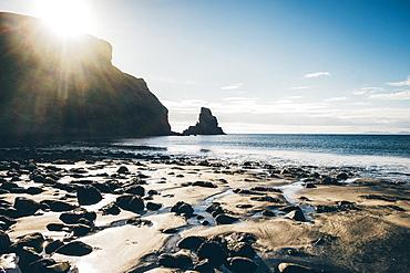 Sandy beach with rocks and cliff, rugged ocean coast, Scotland