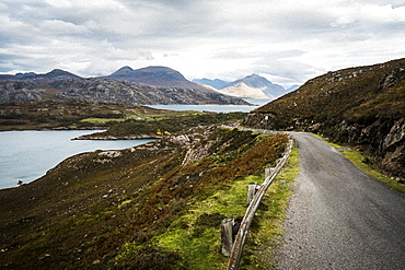 Landscape with rural road cutting through mountains and lochs under a cloudy sky, Scotland