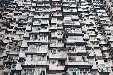 Low angle view of facade of towering residential complex with windows and balconies, China
