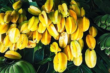Close up of star fruits and green bananas for sale along the side of the road, Guam