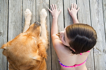A young girl and a golden retriever dog side by side on a jetty, Austin, Texas, USA