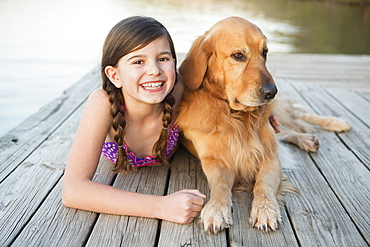 A young girl and a golden retriever dog lying on a jetty, Austin, Texas, USA
