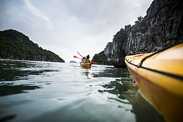Group of kayakers rowing in a bay amidst limestone karst formations, Vietnam