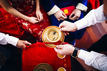 High angle close up of a ritual at a Chinese wedding ceremony, people passing a bowl of soup