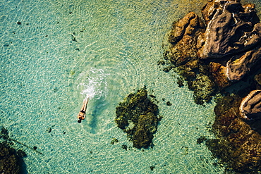 High angle view of woman swimming in the ocean in between rocks, Vietnam