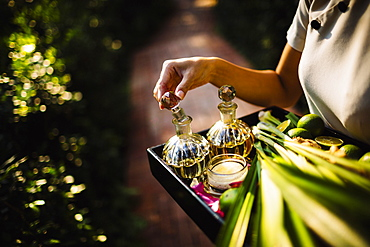 High angle close up of woman holding tray with glass bottles, candles and fruit, Vietnam