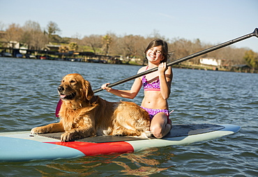 A child and a retriever dog on a paddleboard on the water, Austin, Texas, USA
