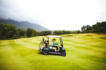 Woman wearing traditional straw hat driving golf cart on the green of a golf course under a cloudy sky