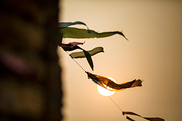 Low angle close up of prayer flags fluttering in the wind at sunset, Laos