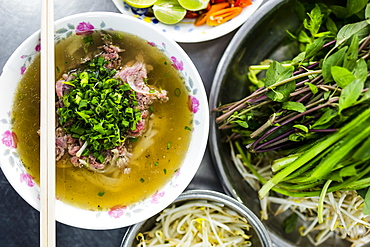 High angle close up of Beef pho, bowl of soup with beef, noodles and vegetables, Vietnam