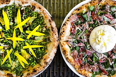 High angle close up of a Burrata Prosciutto pizza with arugala, Vietnam