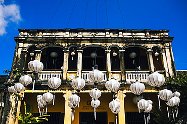 Traditional white lanterns hanging in front of an historic building, Vietnam