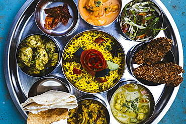 High angle close up of traditional Indian lunch with rice, various curries, pickles, and vegetables, India