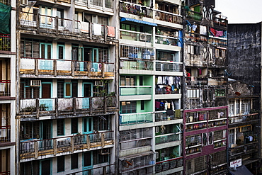 Facade of rows of run down apartment houses with washing hanging on balconies, Myanmar
