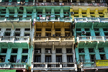 Low angle view of facade of an old apartment building, rows of balconies and windows, Myanmar