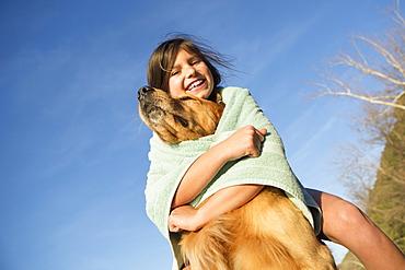 A girl in a beach towel with a golden retriever dog, Austin, Texas, USA