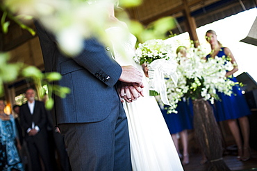 Close up of bride and groom holding hands at a wedding ceremony