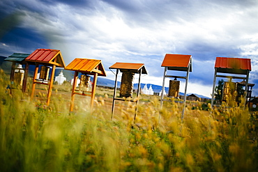 Buddhist prayer drums under small wooden roofs, monuments in the background, Mongolia