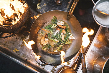 High angle close up of stir fry with prawns and green vegetables in stainless steel wok over flame of charcoal grill, Thailand