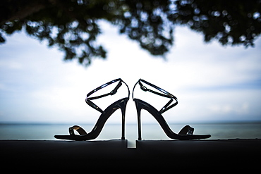 Close up of pair of shiny stiletto sandals, tree foliage and ocean in background, Thailand
