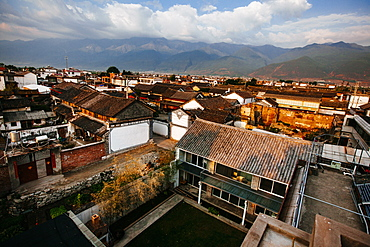High angle view across rooftops of traditional Asian houses, mountains in the distance, China