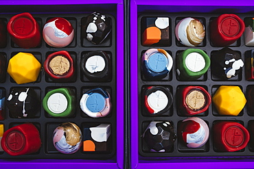 High angle close up of selection of bonbons in a purple and black box, Singapore