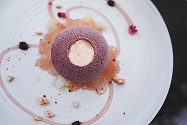 High angle close up of plate of dessert with a cassis bombe and elderflower yoghurt, choya granita and yuzu pearls, Singapore