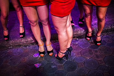High angle view of small group of women wearing red miniskirts and high heels standing on street at night, Thailand