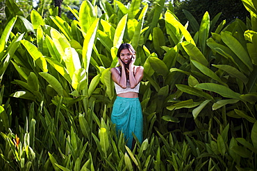 Young woman standing in rain forest with lush green foliage, Thailand