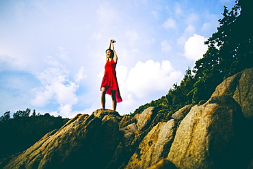 Low angle view of young woman wearing red dress standing on rocks, Thailand
