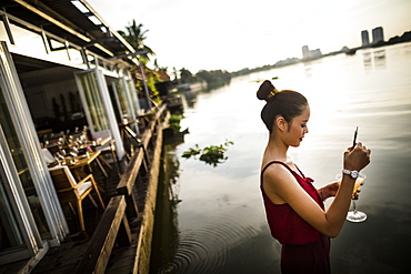 Woman drinking ginger-lemongrass martini at a bar on the banks of a river, Vietnam
