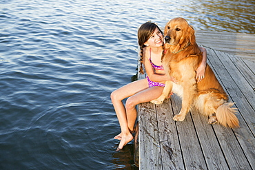 A girl and her golden retriever dog seated on a jetty by a lake, Austin, Texas, USA
