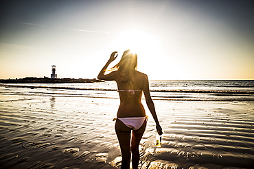 Rear view of woman walking toward the beach during sunset, Thailand