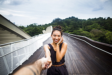 Smiling young woman standing on a bridge, holding man's hand, Singapore