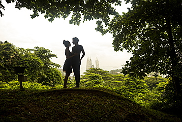 Silhouette of young couple standing underneath trees in a forest, skyscrapers in the distance, Singapore