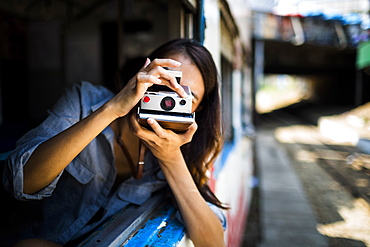Young woman riding on a train, looking out of window, taking picture with old Polaroid camera, Myanmar
