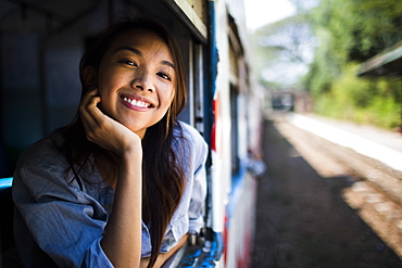 Smiling young woman riding on a train, looking out of window, Myanmar