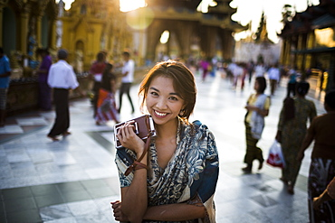 Young woman standing in town square, holding old Polaroid camera, smiling at camera, Myanmar